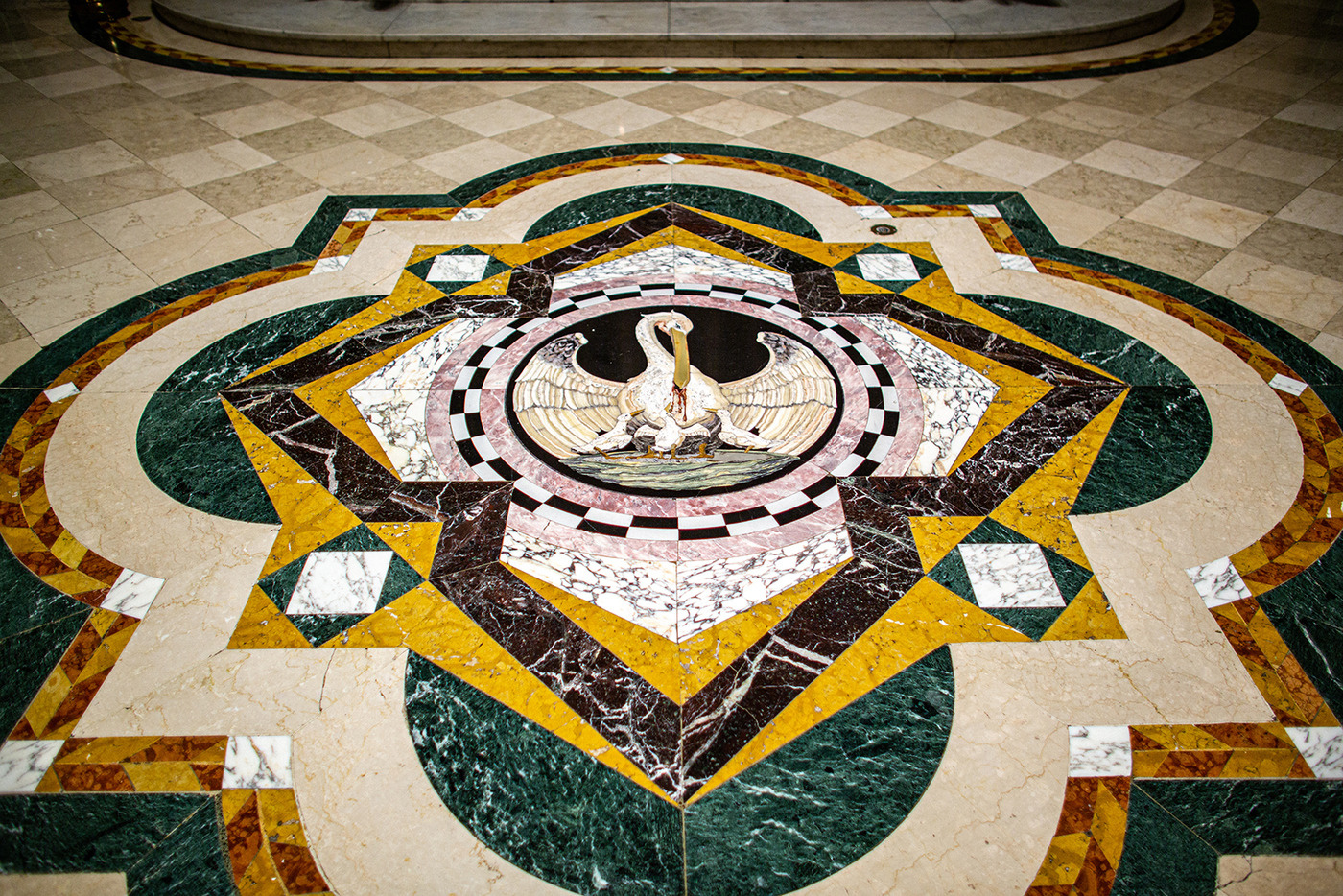 The floor's exquisitely detailed marble mosaic depicts a pelican piercing her breast to feed her young with her own blood, an early symbol of Christ